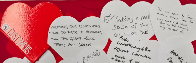 A series of heart shaped papers containing the voices of team members who participated in voice of the customer (VoC) research.